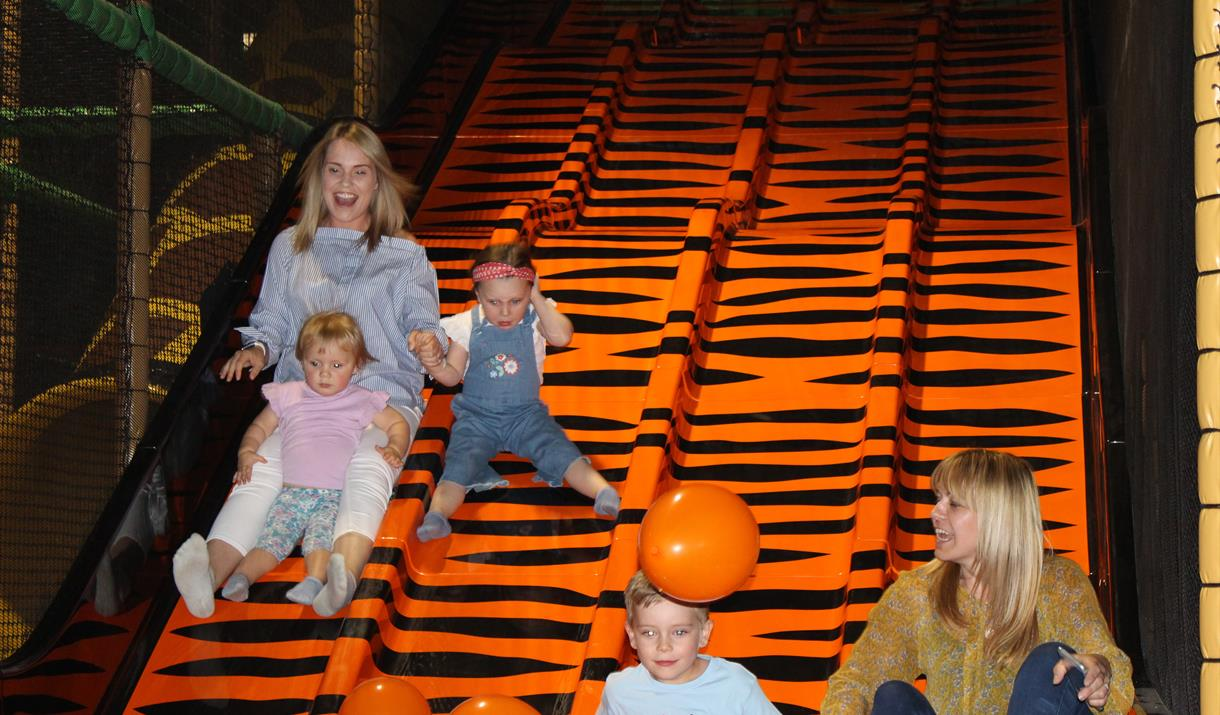 Family going down a slide at Safari Play!