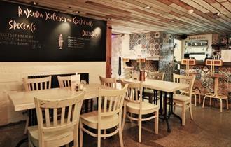 The inside of Bar Rakuda showing tables, chairs and a blackboard menu.
