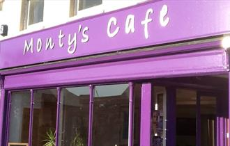 The purple shop front of Monty's showing large windows and the café name.