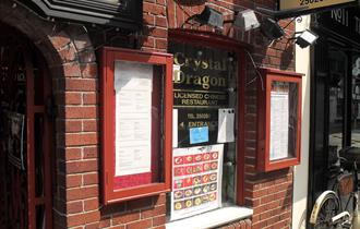 The red brick exterior of the restaurant with menus in red glass cases, pictures of various dishes and signage.