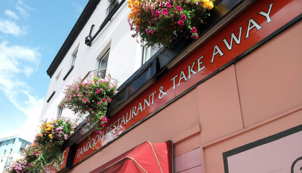 The painted outside of the restaurant with a sign saying Tandoori Restaurant  & Take Away. An awning and flowering hanging baskets are also seen