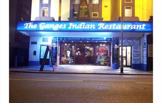 Front of the restaurant showing a brightly lit blue sign saying The Ganges Indian Restaurant.