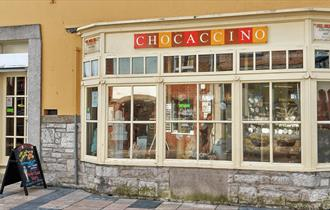 The outside of Chocaccino showing signage and glass display windows with goods displayed inside.