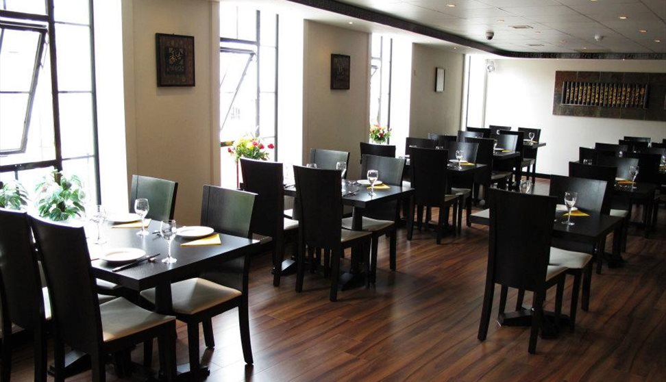 The inside of the restaurant with multiple chairs and tables set for a meal.
