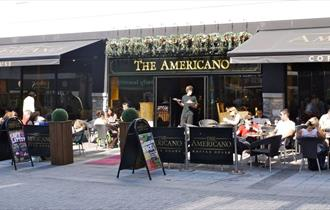 The outside of the Americano Coffee house showing the outdoor seating areas and customers enjoying food and drink.