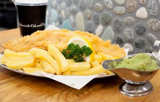 A plate of fish and chips garnished with lemon and parsley and a jug of mushy peas.