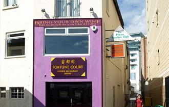 The purple painted outside of Fortune Court showing the entrance and adjacent alleyways.