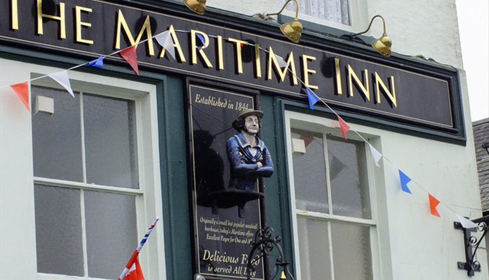 The pale green painted outside of The Maritime Inn with a painted figurehead affixed to the building and Union Jack bunting.
