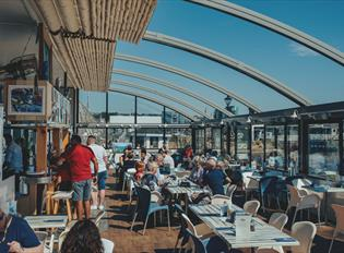 Inside the Boathouse Café with the roof retracted. Customers sitting at tables with a blue sky and views over Sutton Harbour.