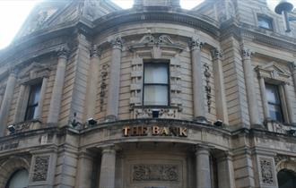 The stone exterior of The Bank with stone pillars and arches and a metal sign saying The Bank.