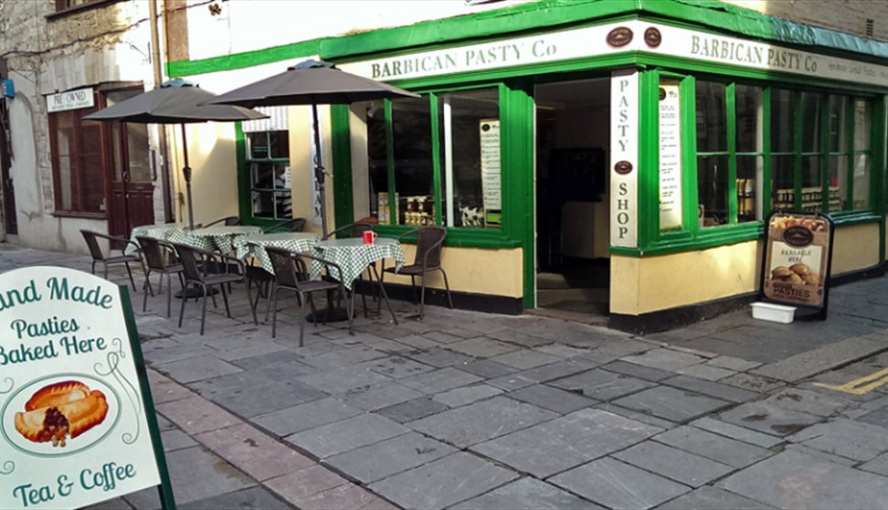 The green, white and yellow painted outside of the Barbican Pasty Co. with outside seating and tables and a sign.