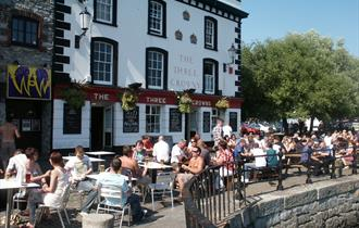 Customers in summer attire sat outside the Three Crowns at outdoor tables and chairs next to the harbour.