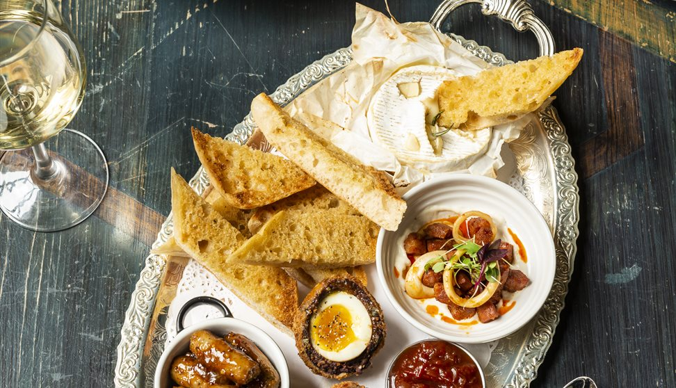 A large platter of buffet food, including scotch eggs, cocktail sausages, pickle, toasted bread and dips.