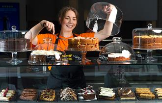 A large glass display counter with large cakes and cake slices displayed. A waitress in an orange top lifting the lid from a glass dish.