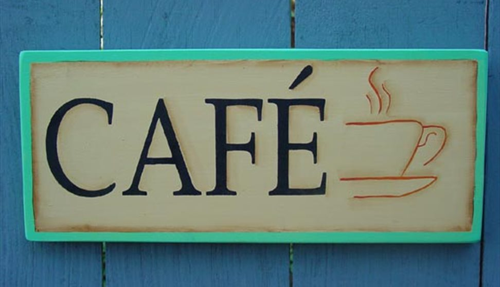 A sign bearing the word CAFE and a picture of a steaming cup of coffee. This hung on a blue painted fence.