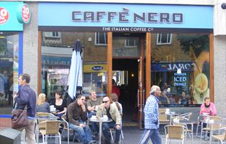 Seating area with tables, chairs and umbrellas outside Caffe Nero.