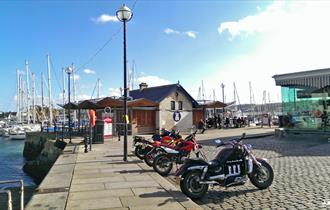 A distant shot of Cap'n Jaspers at the end of the quay with yachts in the background and motorbikes parked outside.