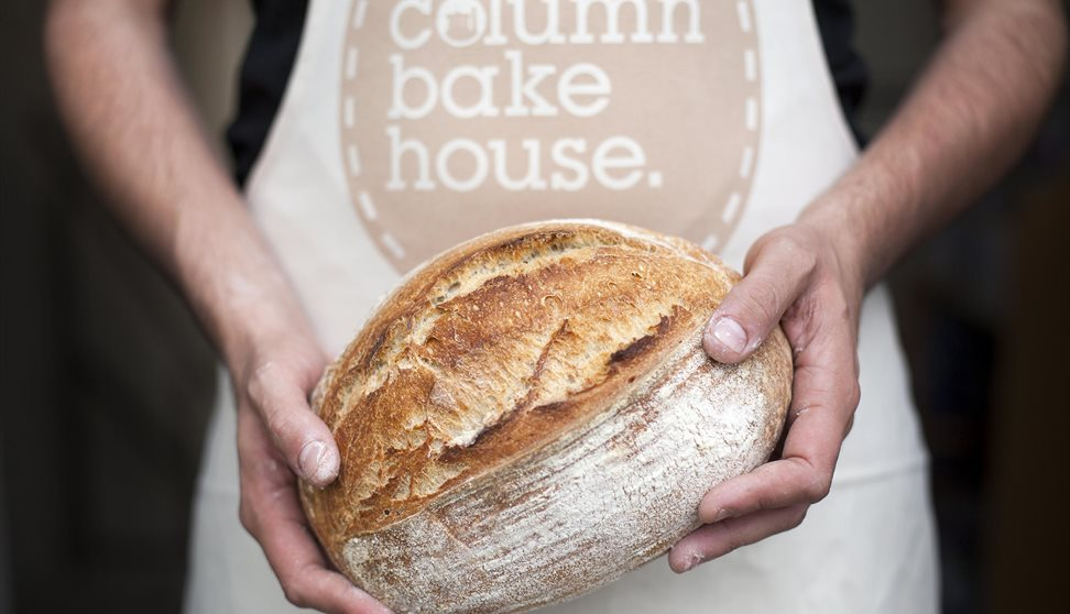 """A baker wearing an apron with the words """"Column Bakehouse"""" printed on it and holding a freshly baked loaf of bread."""