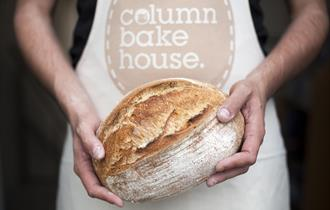"A baker wearing an apron with the words ""Column Bakehouse"" printed on it and holding a freshly baked loaf of bread."