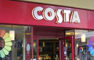 An external shot of Costa showing the shop front windows and the large Costa sign.