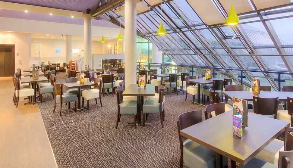 Dining area at China Fleet set up with tables and chairs and a glass wall with views over the club.