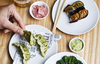 Small white plates of different foods displayed on a table with chopsticks and a hand holding a green gyoza.