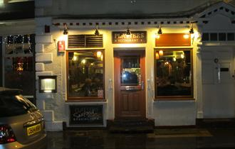 The lit outside of Platters restaurant with a car parked outside and a well lit sign over the door saying Platters.