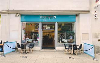 Seating area on the pavement outside Moments Café with tables and chairs.