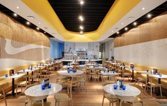 The bright interior of Pizza Express set for diners with chairs, tables with menus and blue glasses on.
