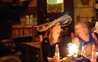 Diners sat at a table with a birthday cake with lit sparkler and a lady smiling and wearing a sombrero.