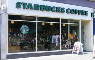 The exterior of Starbucks showing the shop windows and Starbucks  Coffee sign.