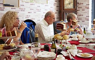 People sat at tables inside the tea rooms eating afternoon tea served from tiered cake stands.