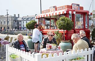 Red vintage Coffee and Donuts van with striped awning, outdoor seating area with Potted trees, white picket fence and customers sat at tables.