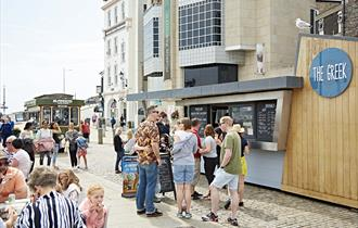 Customer queuing outside The Greek also customers sat at outdoor seating area.