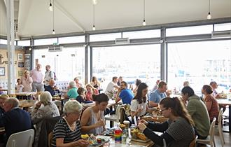 Busy inside of the restaurant showing tables full of diners in front of glass walls with views over Sutton Harbour.