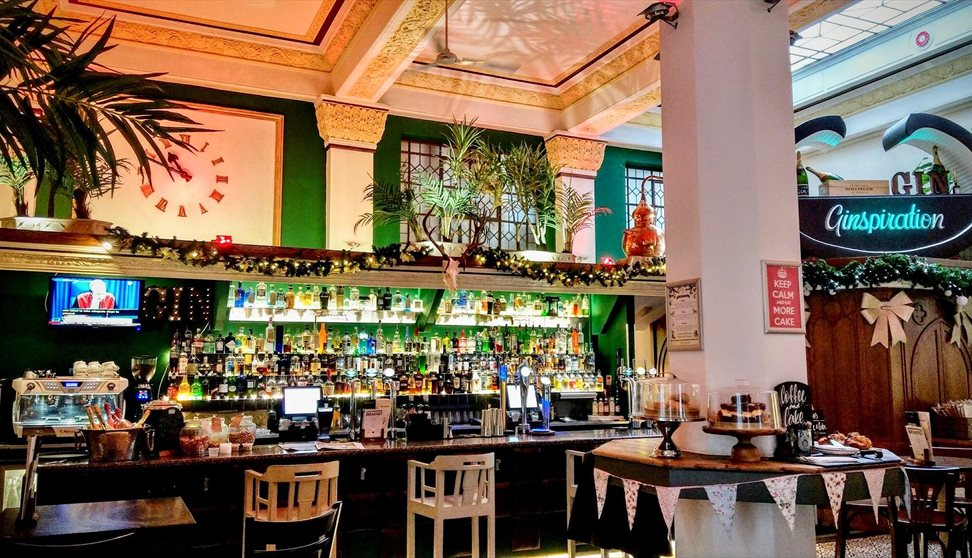 The bar area inside The Treasury, showing large stone pillars, large plants, a large wall clock and lots of bottles of drink displayed.