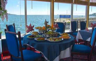 A table inside the restaurant set for a meal with dishes of food in front of large glass windows overlooking the water of Plymouth Sound.