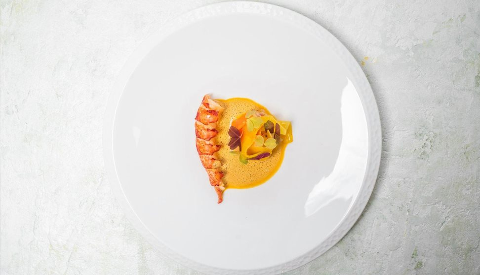 A white plate with a brightly coloured shellfish dish arranged on it.