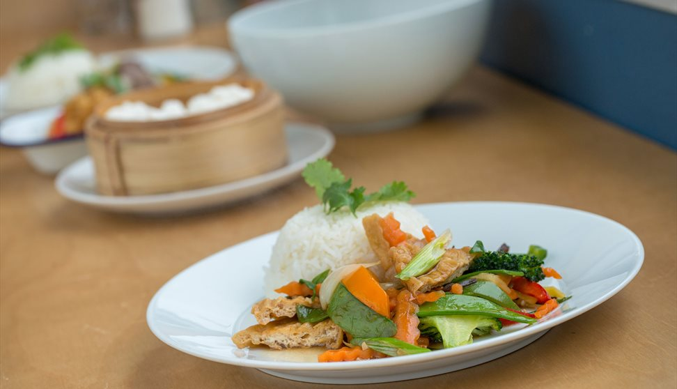 A plate with rice and stir fried vegetables. A bamboo steamer containing rice is also on the table.