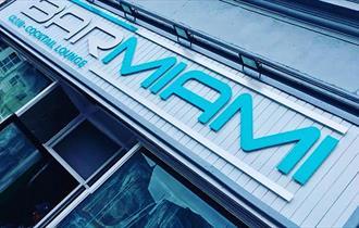 The turquoise signage outside Bar Miami.
