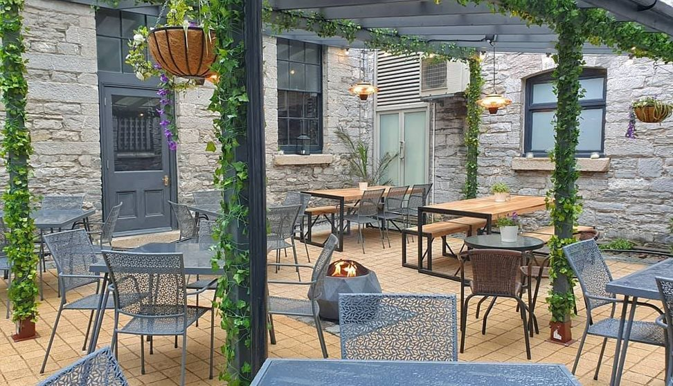 Outside courtyard area with tables and chairs, a fire pit and a plant covered pergola.