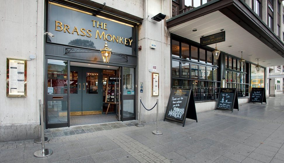 The entrance to the Brass Monkey with chalkboards on the pavement outside.