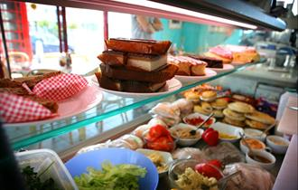 Large refrigerated display cabinet inside shop window displaying cakes, slices, pies and sandwich ingredients.