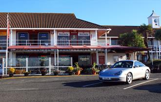 The outside of Chandlers with potted plant displays and a parked car.