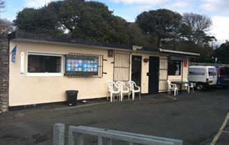 The outside of Devil's Point Café showing an ice-cream menu, chairs and parking.