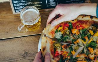 A large pizza divided into portions being pulled apart by a pair of hands. On the table is also a glass of beer and a menu.