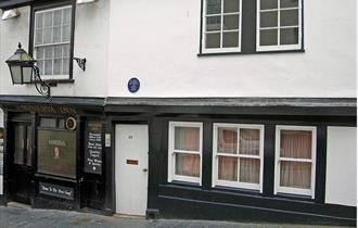 The black and white painted exterior of the Minerva Inn with large lantern hanging outside above the pavement.