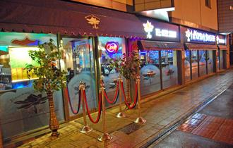 A brightly lit night time shot of the outside of the restaurant showing the entrance and pavement outside.