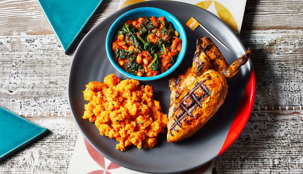 A grey plate with a portion of chicken, sweet potato mash and a green pot of beans and spinach.