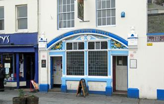 Exterior of The Dolphin with blue painted exterior, stain glass windows and painted dolphins.
